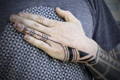 Tatuaje tribal en brazo y mano
