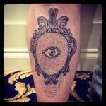Pluma azul tatuada en brazo
