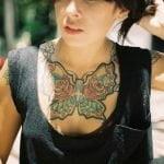 Mariposa tatuada en el pecho de una joven