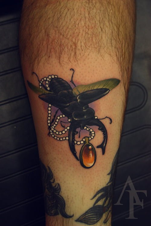 Tatuaje escarabajo con dije de ambar
