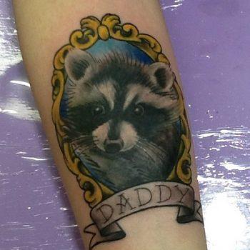 Tatuaje de mapache en brazo