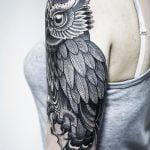 Búho tatuado en hombro de mujer