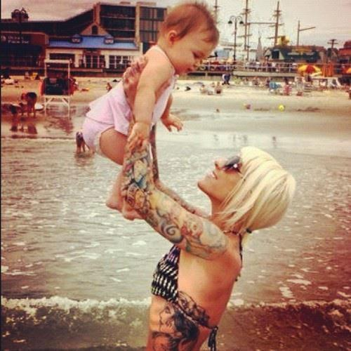 photo of a girl with tattoos holding her baby