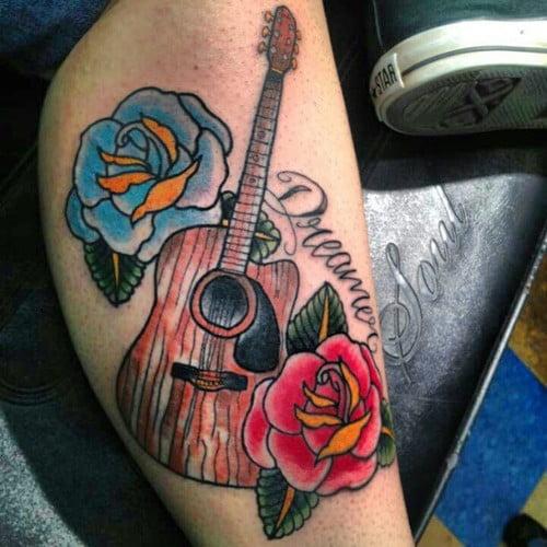 39 dreamer 39 un tatuaje de una guitarra con flores alrededor