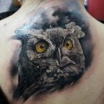 Búho tatuado en la espalda