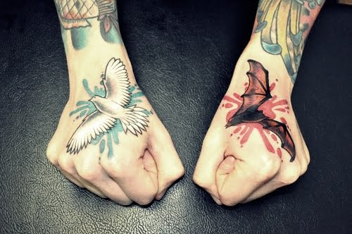 Bat and dove tattoo on fists