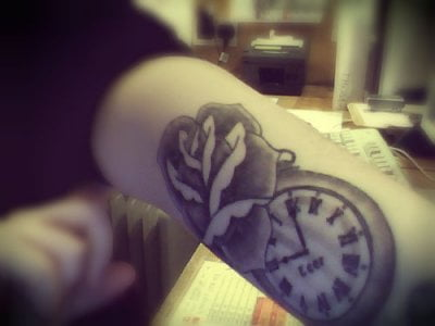 Rose and clock tattoo on arm