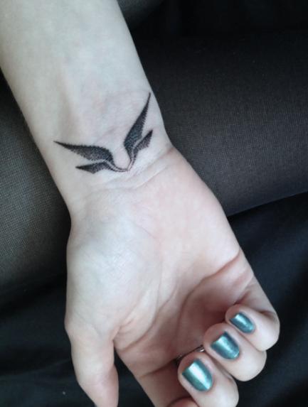 Par de alas tatuadas en muñeca