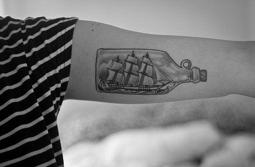 Tatuaje barco en botella en el brazo