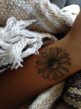 Tatuaje flor con Yin Yang en el brazo