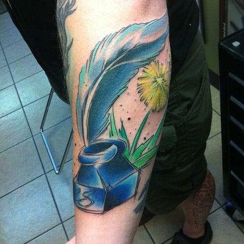 Tatuaje pluma y tintero en el brazo