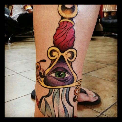 Daga con un ojo tatuada en pierna