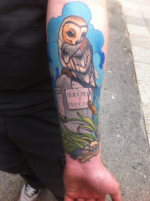 Tatuaje de una lechuza posando en una lápida