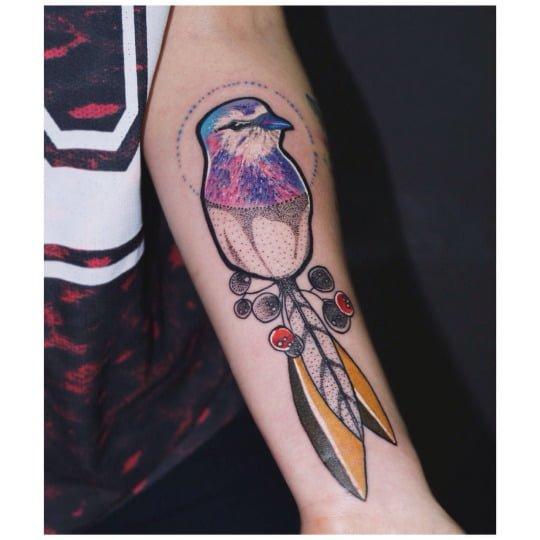 Tatuaje pájaro multicolor en el brazo