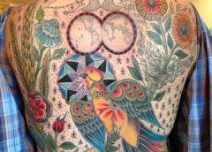 Tatuaje pájaro multicolor en la espalda