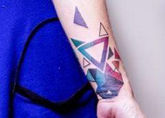 Tatuaje triángulos de colores en el brazo